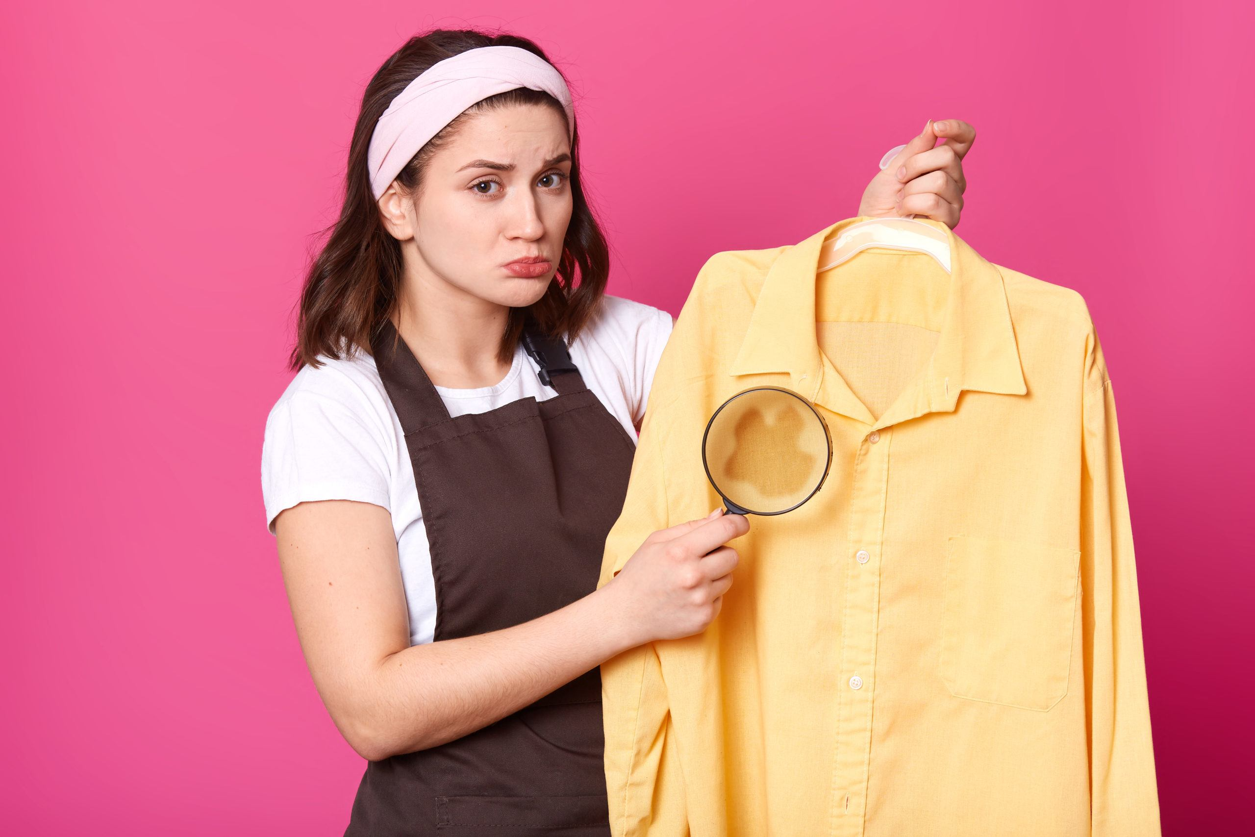 Brunette housewife holds yellow shirt after laundry with coffee stain on fabric, having magnifying glass in one hand. Emotional cute young model wearing brown apron, white t shirt and headband.