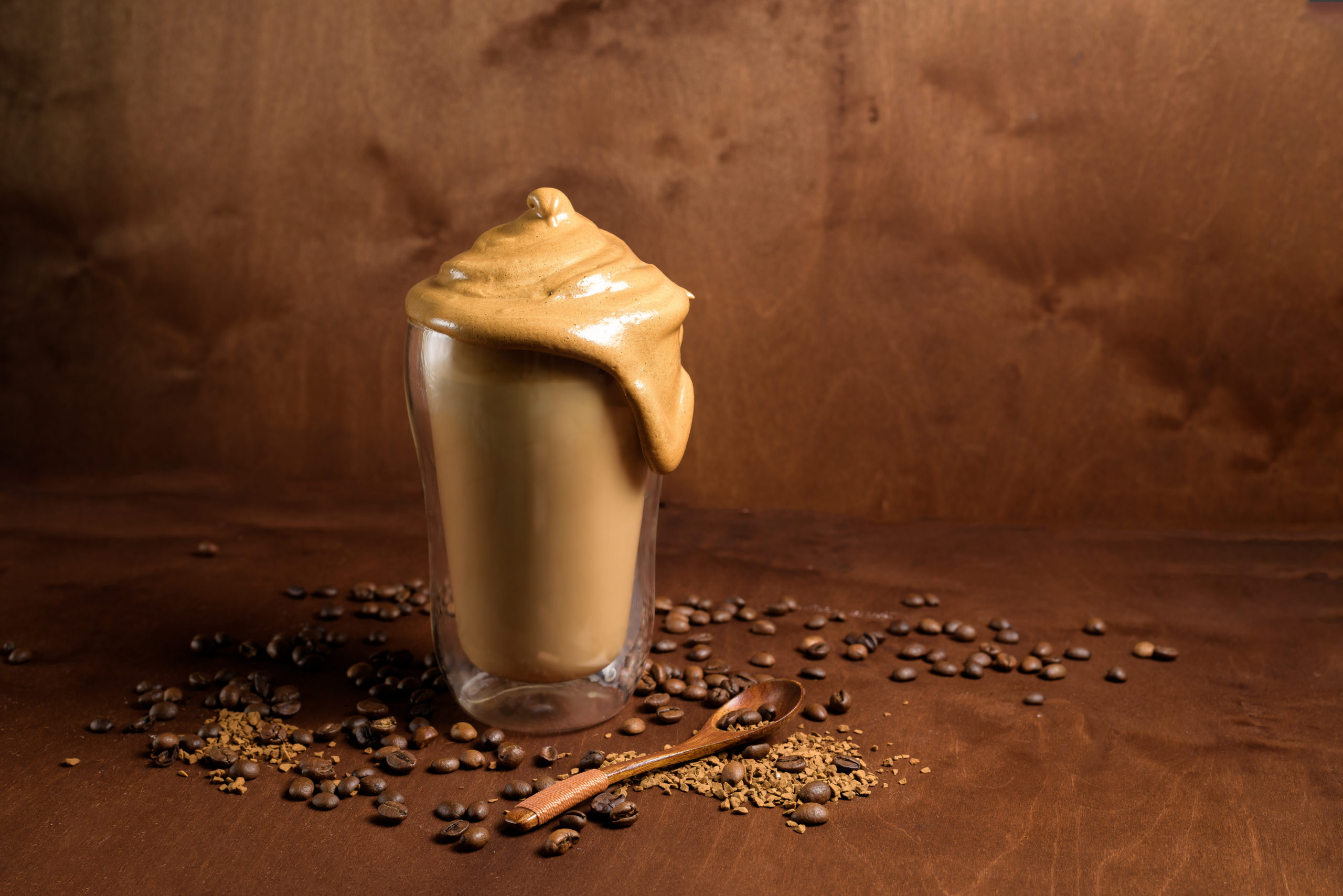 cold dalgon coffee in clear glasses on a dark wooden background. foam from sugar and instant coffee is whipped with a mixer over cold milk. Korean and Indian whipped coffee